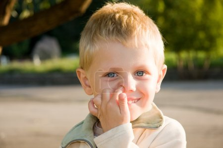 Boy picking his nose outdoors