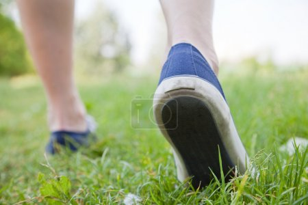 Photo pour Femme marchant sur l'herbe verte dans des chaussures de sport - image libre de droit