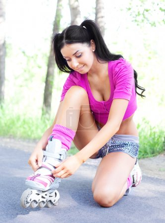 Photo for Happy young brunette woman fastening the roller skates and is getting ready to ride in the park - Royalty Free Image