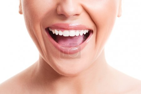 Photo for Closeup of the face of a young woman with healthy white teeth, isolated against white background - Royalty Free Image
