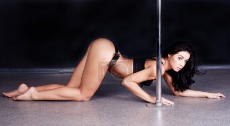 Photo for Young sexy pole dance woman against dark background - Royalty Free Image