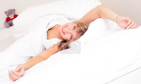 Photo for Beautiful happy young blond woman in bed at home waking up and stretching - Royalty Free Image