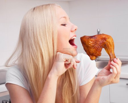 Photo for Beautiful young blond woman eating chicken in the kitchen at home - Royalty Free Image