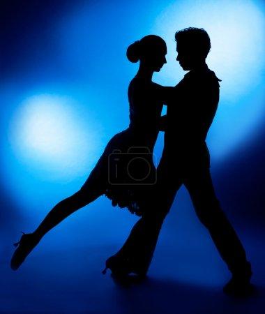 Photo pour Une silhouette d'un couple dansant sur fond de studio bleu - image libre de droit
