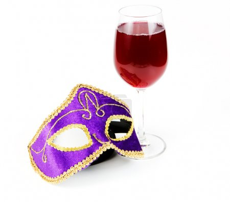 Glass of red wine and the Venetian mask on a white background
