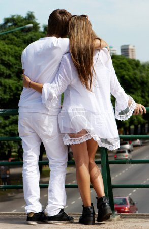 Photo for Loving couple standing and hugging against in city. - Royalty Free Image