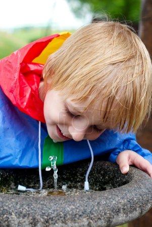 Photo pour Le petit garçon l'eau potable dans le parc - image libre de droit