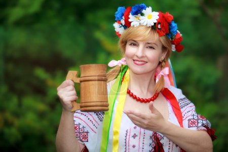 Happy Ukrainian woman with a wooden mug