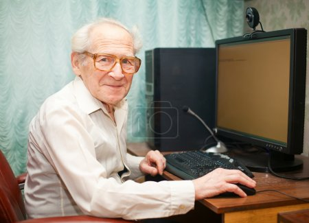 Photo for Smiling happy old man sitting near computer and holding mouse - Royalty Free Image