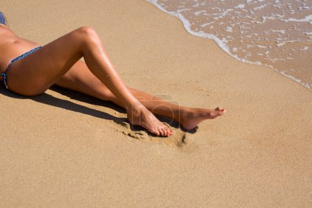 Photo for Tanned young woman in bikini lying on beach - Royalty Free Image