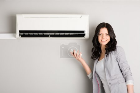 Photo for Beautiful girl holding a remote control near the air conditioner - Royalty Free Image