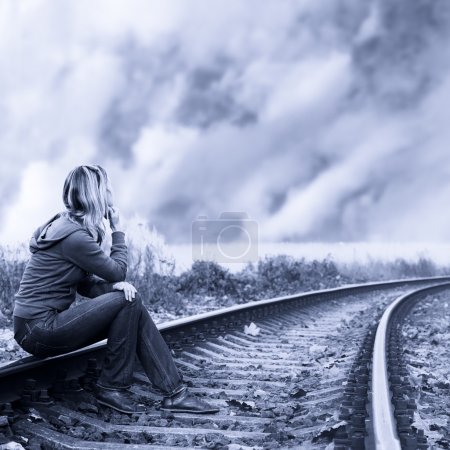 Photo for Lonely woman sitting on the rails and thinking. - Royalty Free Image