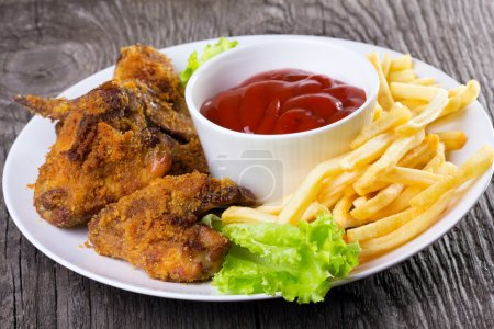 Photo for Chicken wings with sauce and fries - Royalty Free Image