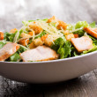 Caesar salad with chicken and greens on wooden tab...