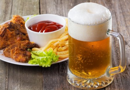 Photo for Cold mug of beer with chicken wings - Royalty Free Image