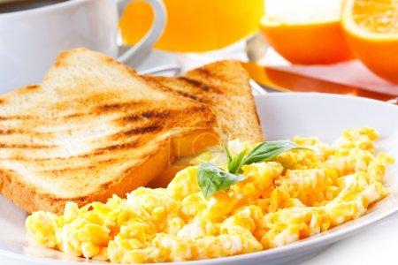 Photo pour Petit déjeuner avec œufs brouillés, toasts, jus de fruits et café - image libre de droit