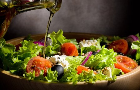 Photo for Vegetable salad with olive oil pouring from a bottle - Royalty Free Image