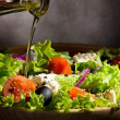 Vegetable salad with olive oil pouring from a bott...