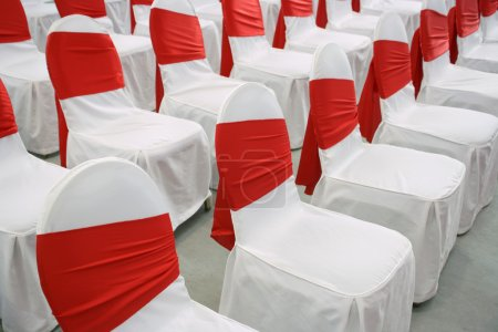 Photo for Event chairs with white and red decoration lined up in row - Royalty Free Image