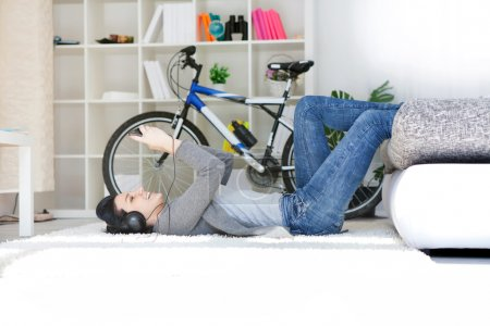 Smiling woman listening music lying on floor in th...