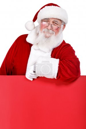 Photo for Santa Claus leaning on blank red billboard, isolated on white background - Royalty Free Image