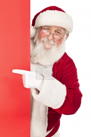 Photo for Smiling Santa Claus pointing in red blank sing , isolated on white background - Royalty Free Image