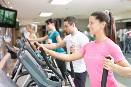Photo for Young training on simulators in gym - Royalty Free Image