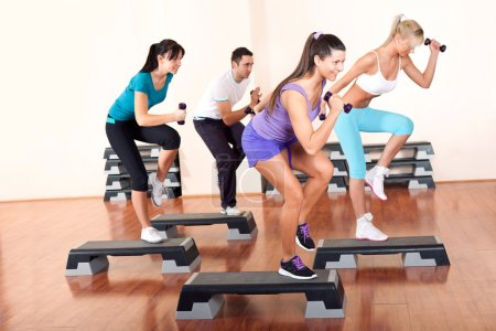 Photo for Young stepping with dumbbells in gym - Royalty Free Image