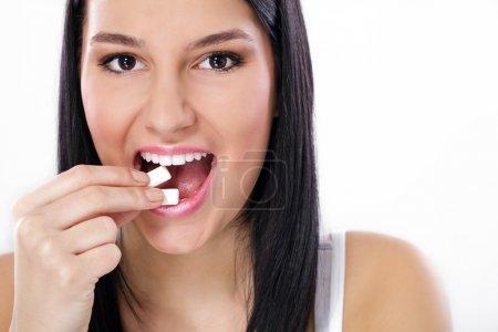 Beautiful girl taking white chewing gum, smiling
