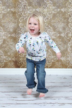 Photo for Adorable little girl jumping in air in studio - Royalty Free Image