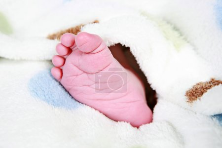 Photo for Babies foot taken closeup with blanket around it - Royalty Free Image