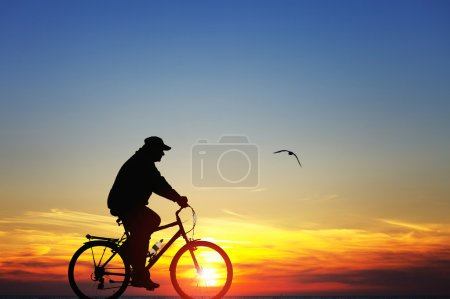 Photo for Silhouette of a man on bike at sunset - Royalty Free Image