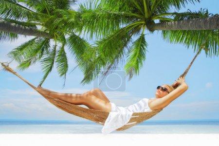 Photo pour Vue de belle jeune femme balançant en hummock sur la plage tropicale - image libre de droit