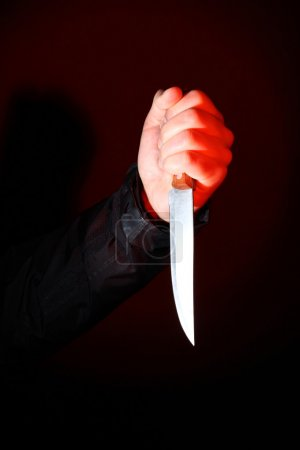 Photo for Hand with knife illuminated by a red spotlight - Royalty Free Image