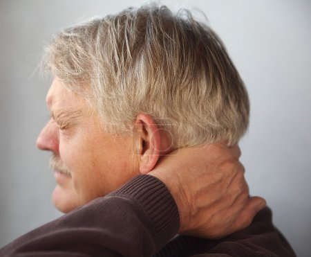 Photo for An older man wincing from pain in the back of his neck - Royalty Free Image