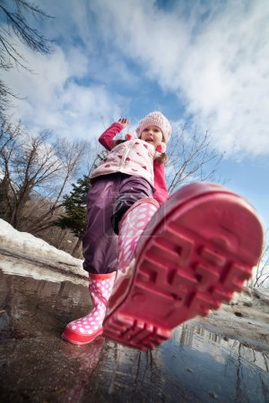 Foto de Un poco chicas Rosa botas chapoteando en un charco de barro - Imagen libre de derechos