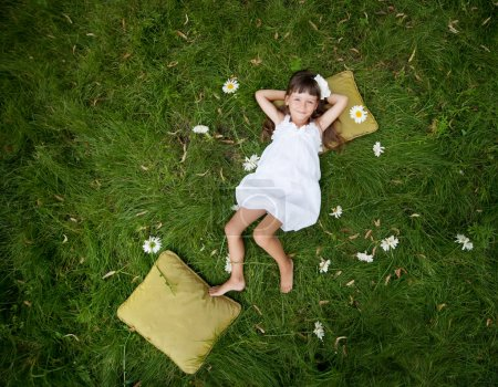 Little girl resting on soft pillow in fresh spring grass