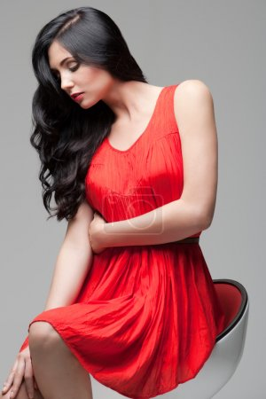 Photo for Young gorgeous caucasian brunette in red dress on the chair, studio shot - Royalty Free Image