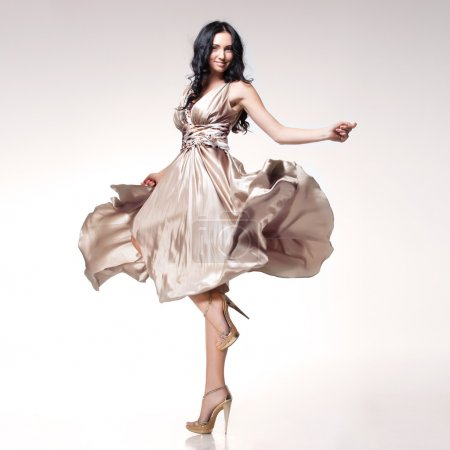 Photo for Young beautiful caucasian brunette in gorgeous dress, motion shot - Royalty Free Image