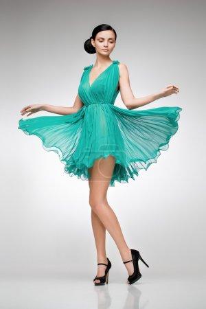 Elegant blonde in green teal posing in the studio...