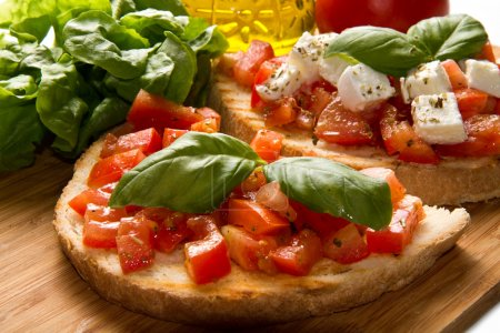Photo for Italian bruschetta with fresh tomatoes, basil, garlic, olive oil and cheese - Royalty Free Image