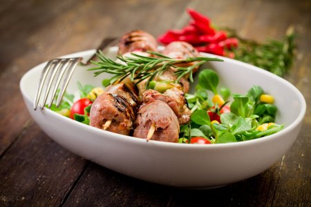Photo for Delicious broiled meat skewers on wooden table with salad - Royalty Free Image