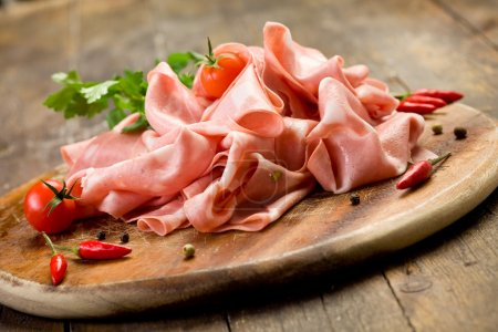 Photo for Wooden chopping board with sliced mortadella and red pepper - Royalty Free Image