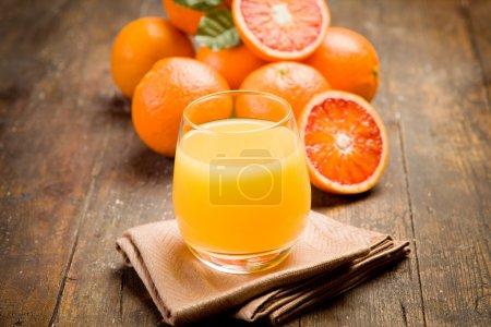 Photo pour Jus d'orange frais pressé sur une ancienne table en bois - image libre de droit