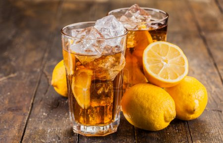 Photo for Lemon ice tea on brown wooden table with lemons around - Royalty Free Image