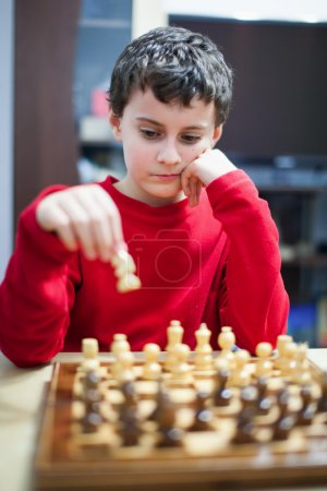 Boy playing chess, selective focus