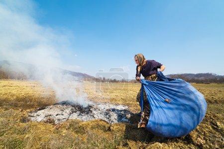 Photo pour Feuilles tombées brûlant de vieille femme rurale, nettoyage dans le jardin de printemps - image libre de droit