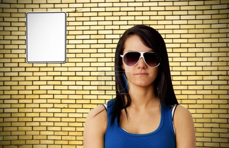 Photo for Tough looking young woman with sunglasses in front of yellow brick wall background with blank white metal sign ready for your text. - Royalty Free Image