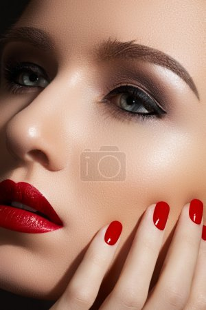 Beautiful close-up portrait of fashion woman model with glamour classic makeup, red lipstick, bright nail polish. Evening style, retro visage and manicure