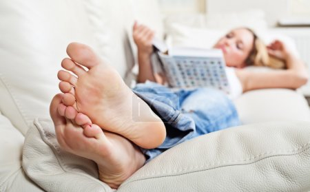 Photo for Barefoot young woman lying on sofa and reading book, shallow depth of field, focus on foot soles - Royalty Free Image